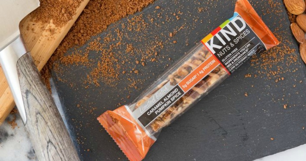 KIND Bar sitting on table with spices, almonds and a knife