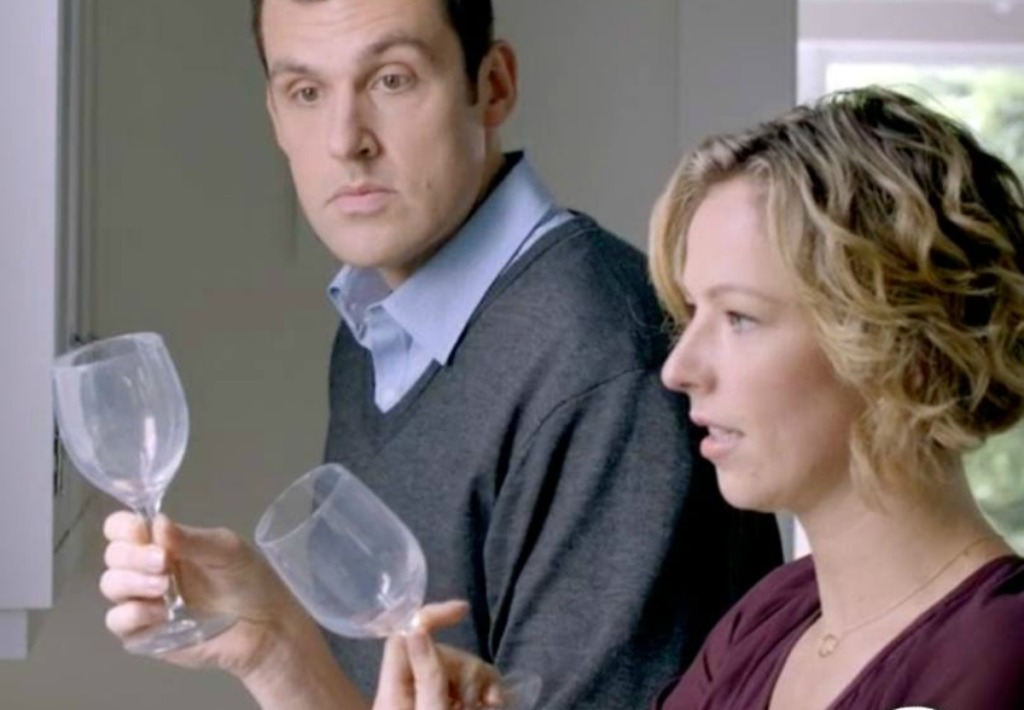 mand and woman looking at cloudy wine glasses