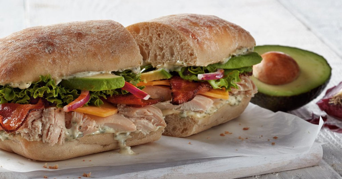 two halfs of boston market Chicken Avocado Club on ciabatta with half of an avocado with pit
