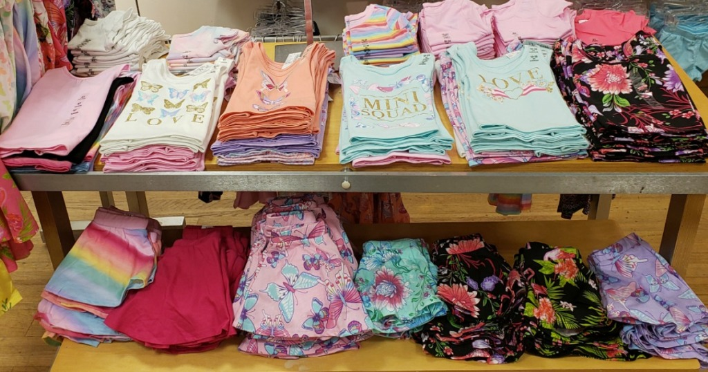 girl's tanks and skirts laying on a table