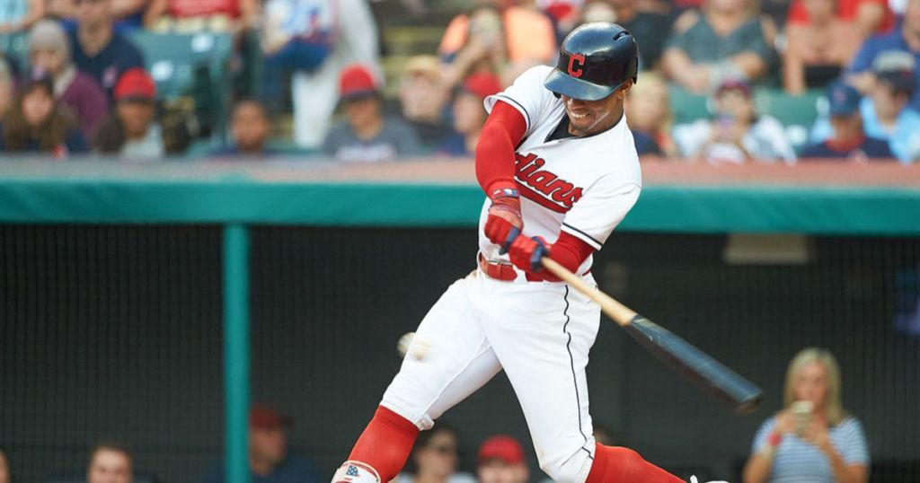 Cleveland Indians player swinging bat with crowd behind him