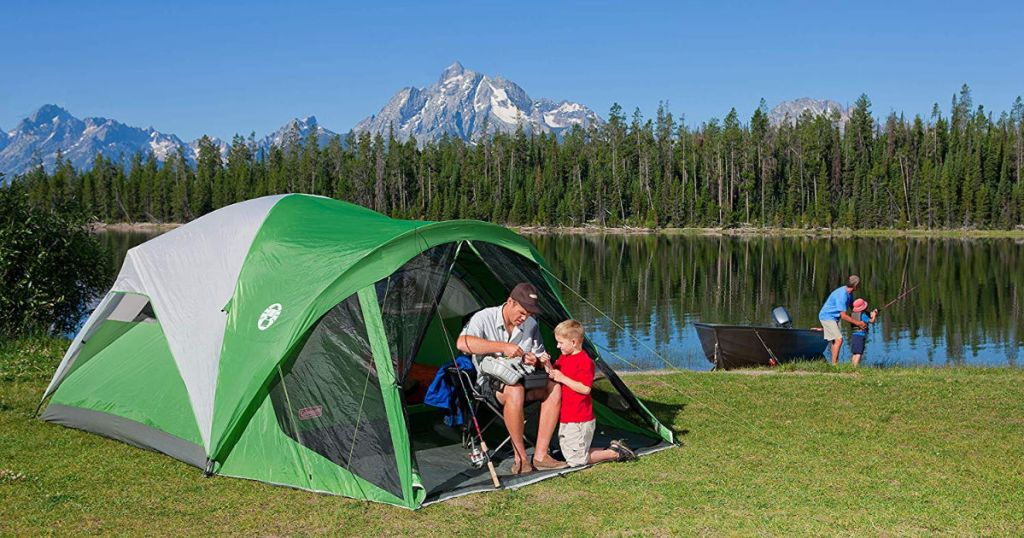 father and son sitting in Coleman Dome Tent camping by a lake with people fishing in the background and the mountains