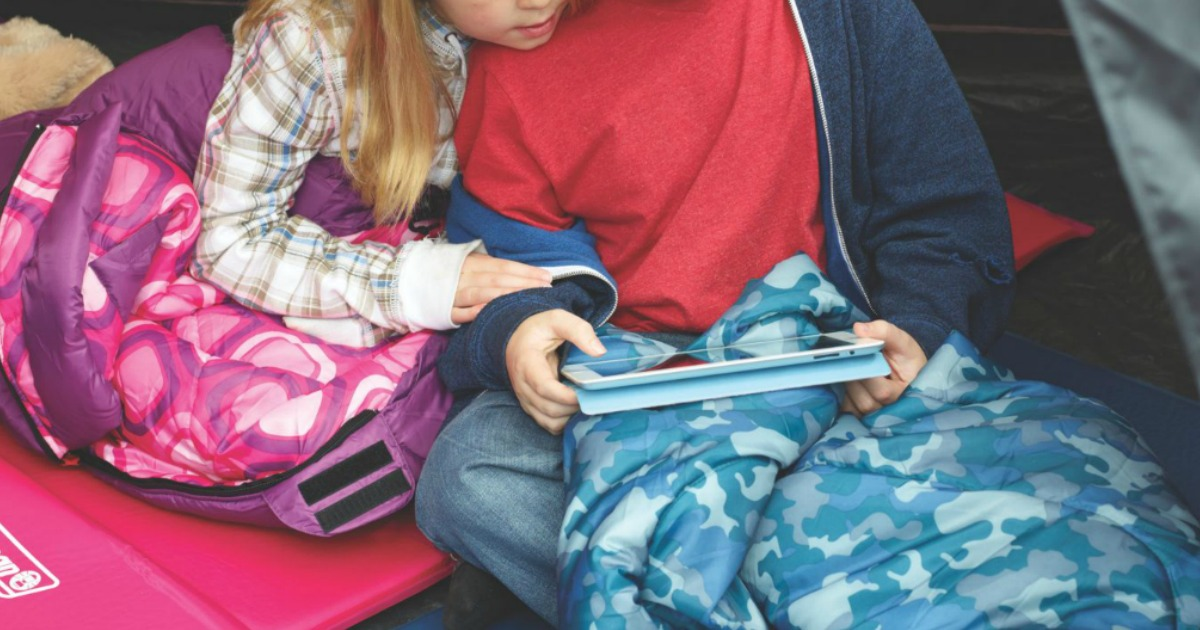 kids sitting in sleeping bags inside a tent looking at a tablet