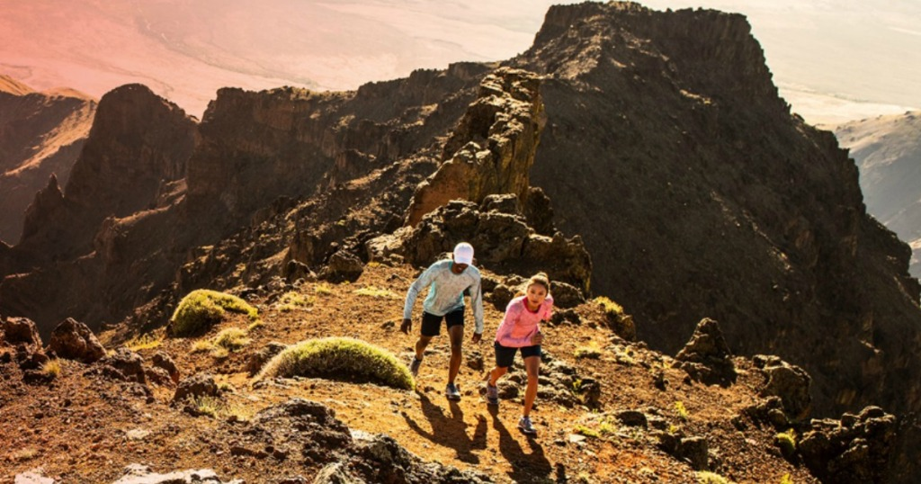 man and woman hiking up a mountain