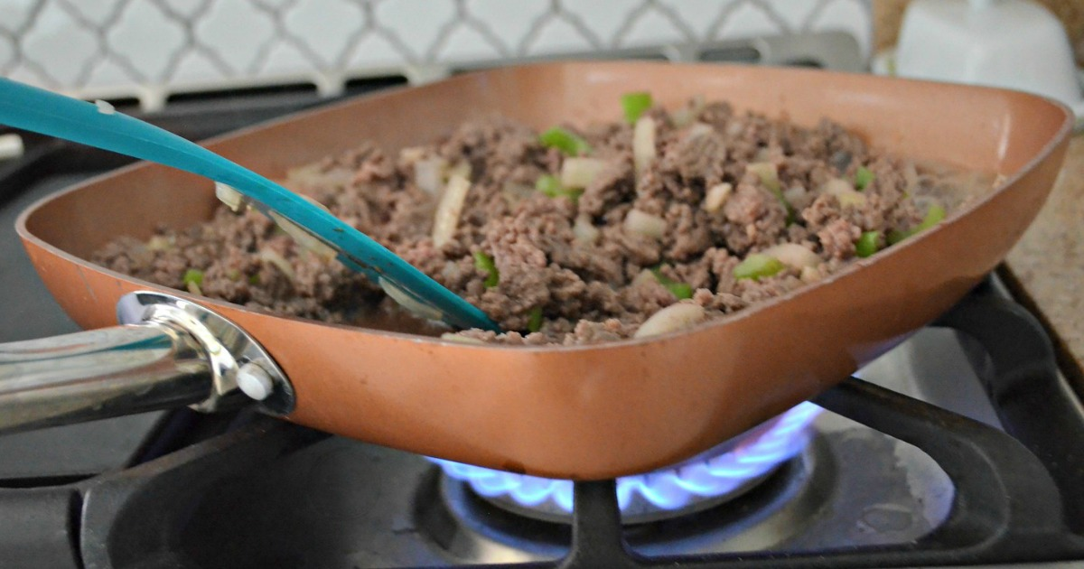 square copper pan over gas stove burner cooking meat and veggies