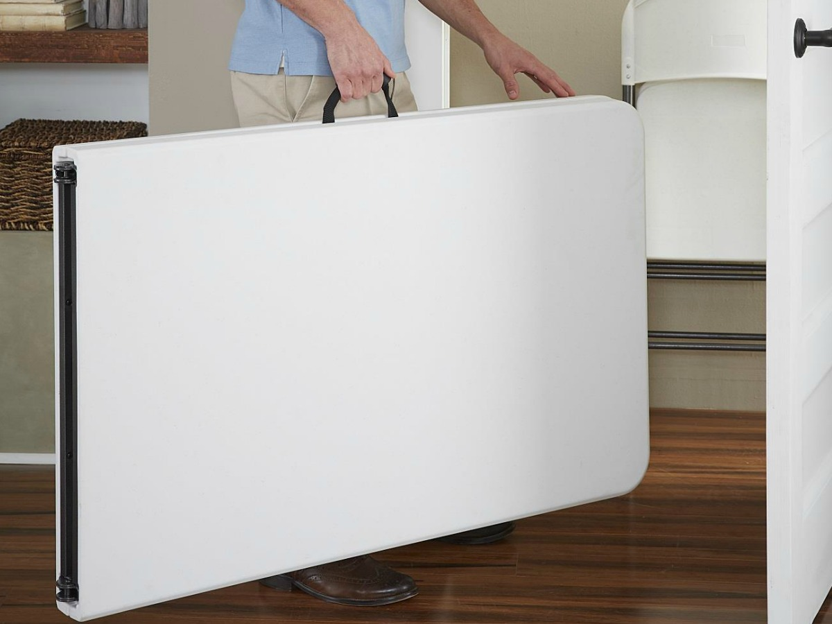 man carrying foldable table to closet