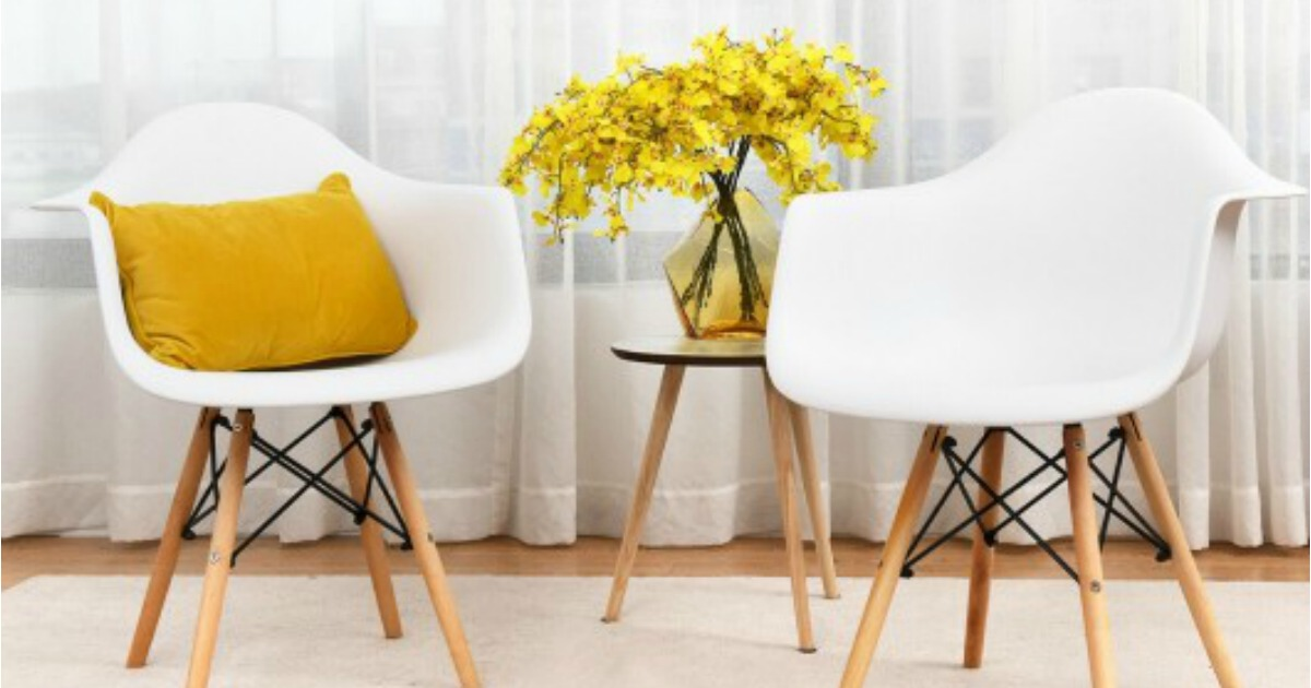 two white midcentury chairs with a yellow pillow arranged in front of curtains