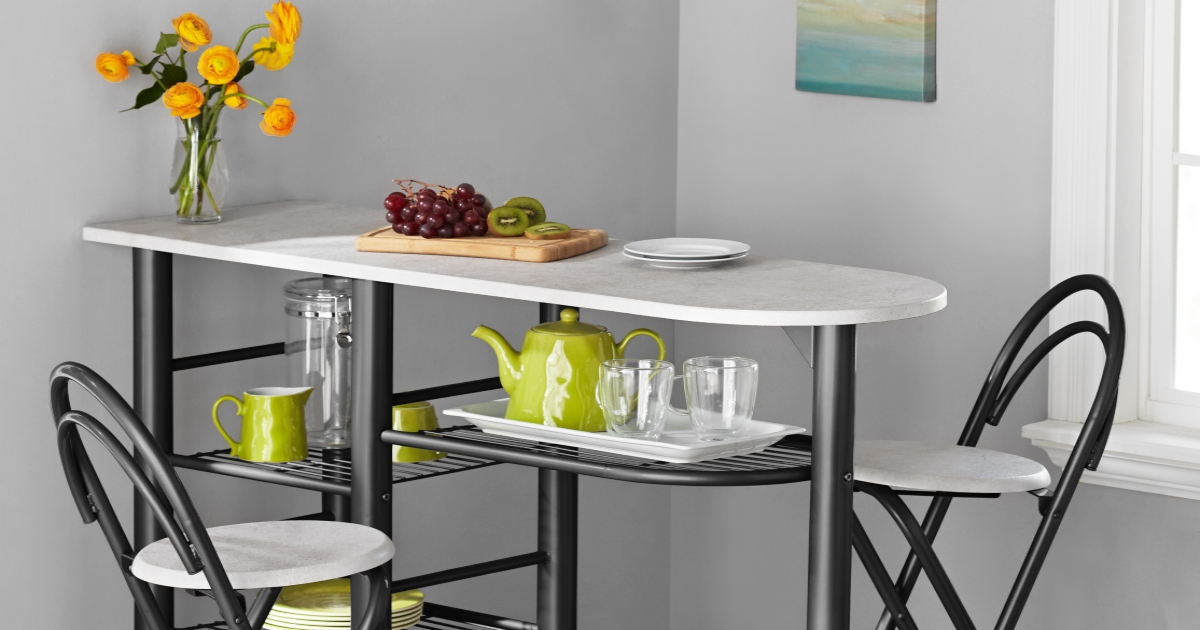 Counter Height Dining set with two chairs, shelving down the side and flowers in a vase with fruit on a plate on top.