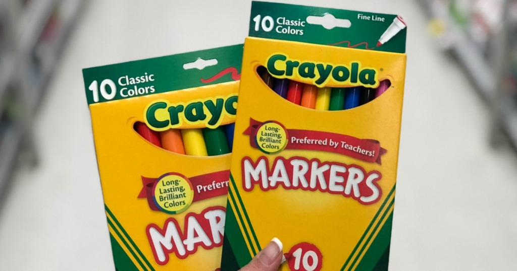 hand holding two packs of Crayola markers