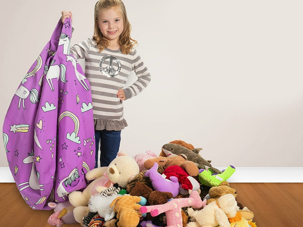 Girl holding empty Creative QT Storage Bean Bag with stuffed animals next to her