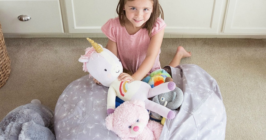 Girl filling her Creative QT Storage Bean Bags with stuffed animals
