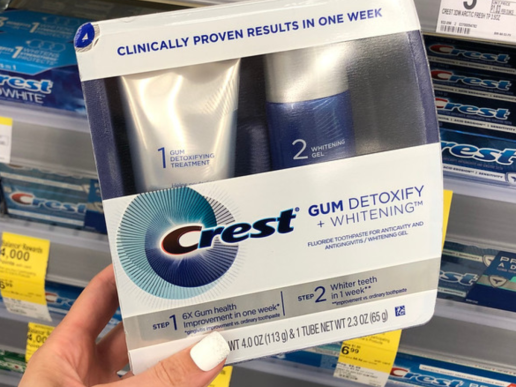 Woman holding Crest Gum Detoxify + Whitening Two-Step toothpaste at Walgreens