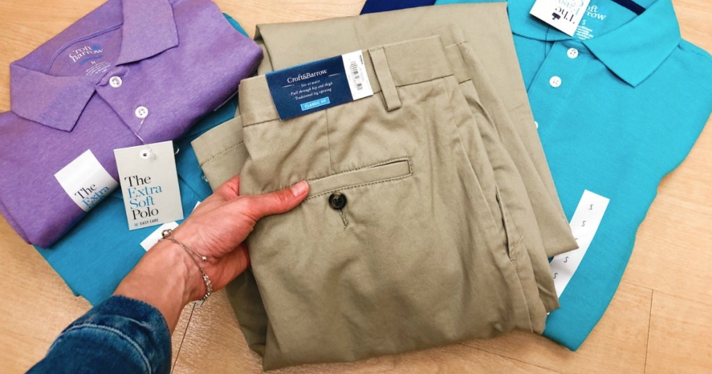 23faaf8d Men's Khaki pants being held by a woman in front of polo shirts at Kohl's