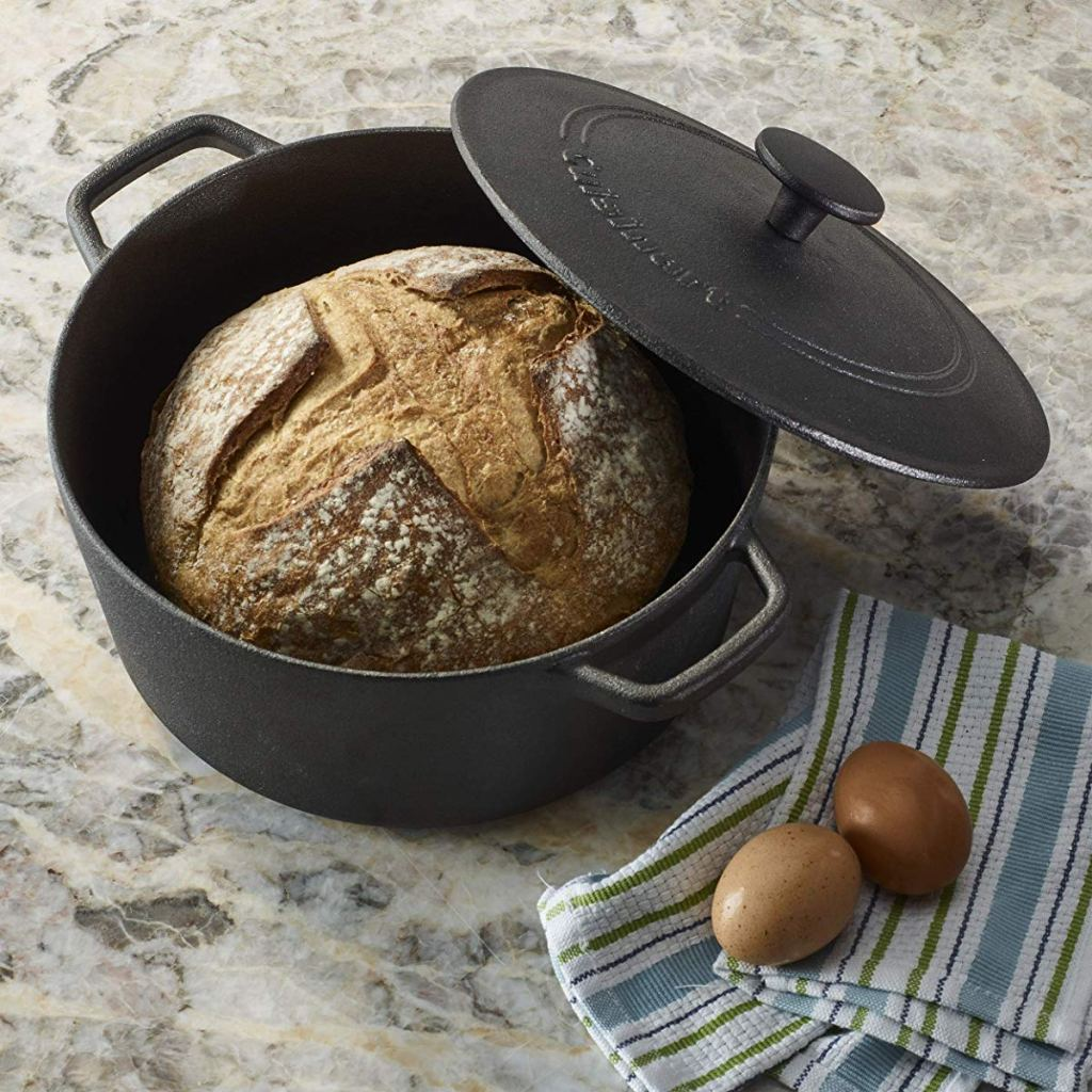 cast iron pan with bread inside and eggs on a towel next to it