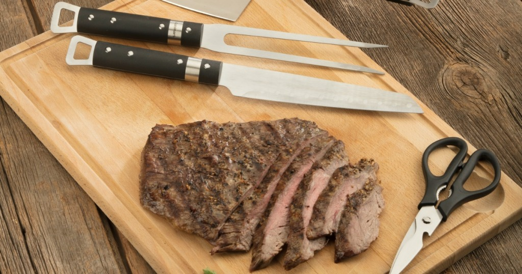 grilling tools next to cut up steak
