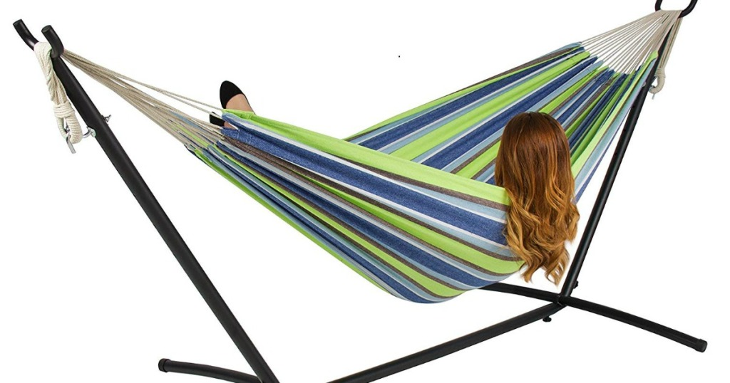 girl laying in blue, green and white striped hammock on metal stand