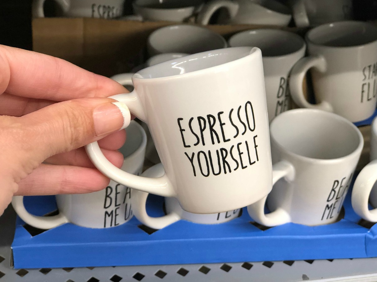 white espresso mugs with espresso yourself written on it being held in a store