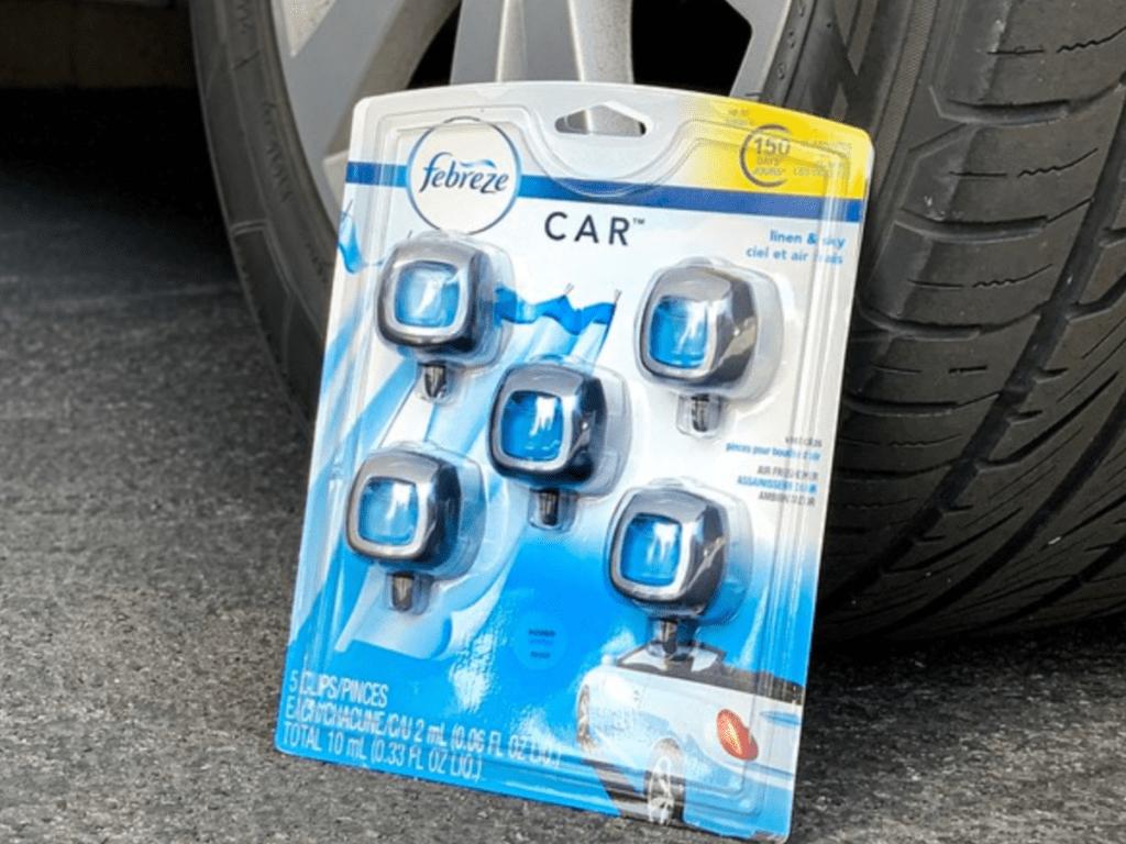 Febreze Car Air Freshener 5 pack leaned on car tire