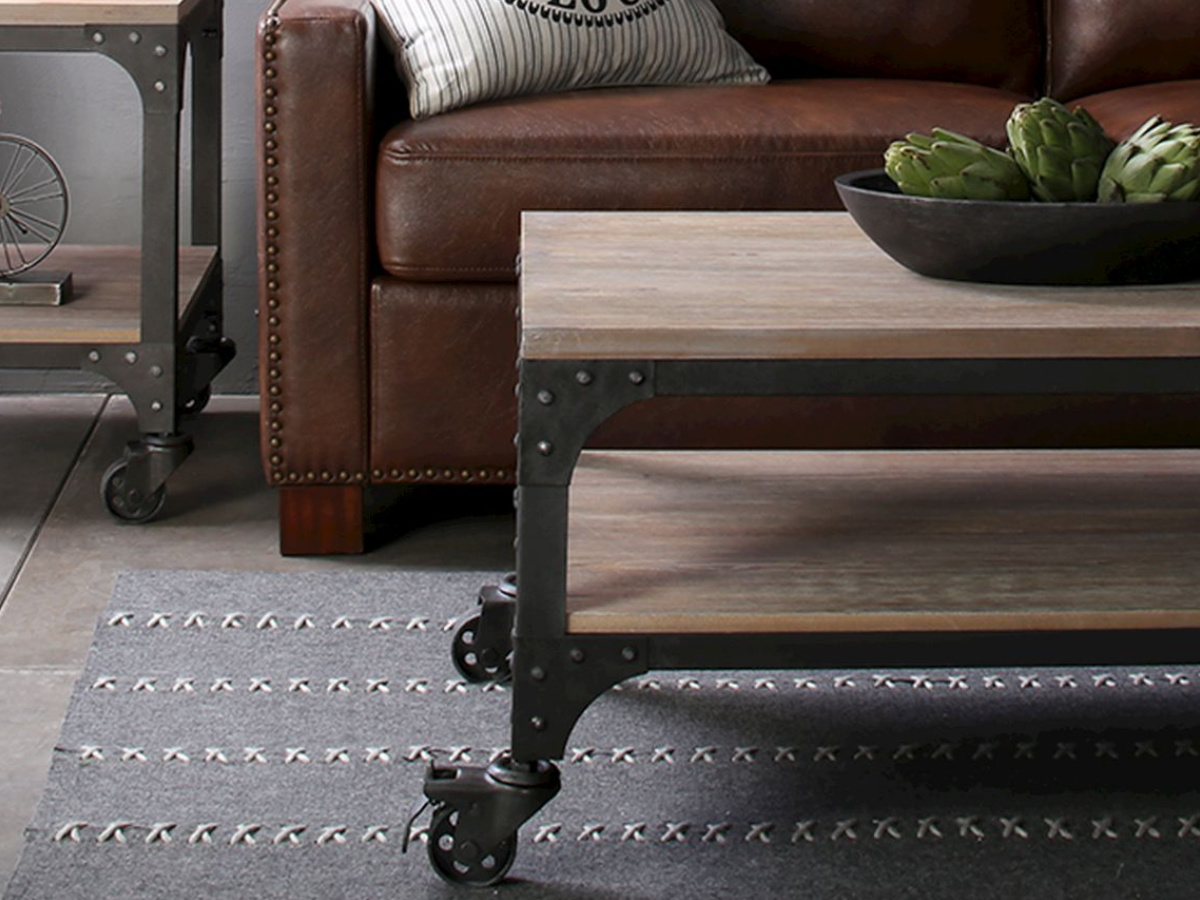 metal and wood coffee table on a rug, in front of a brown couch