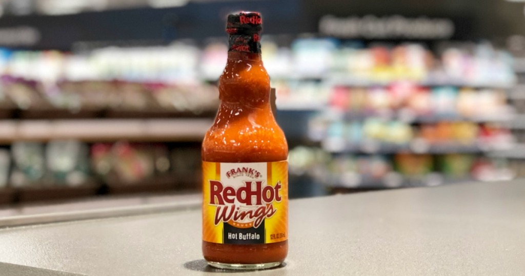 red hot wings hot sauce on counter in store with blurry background