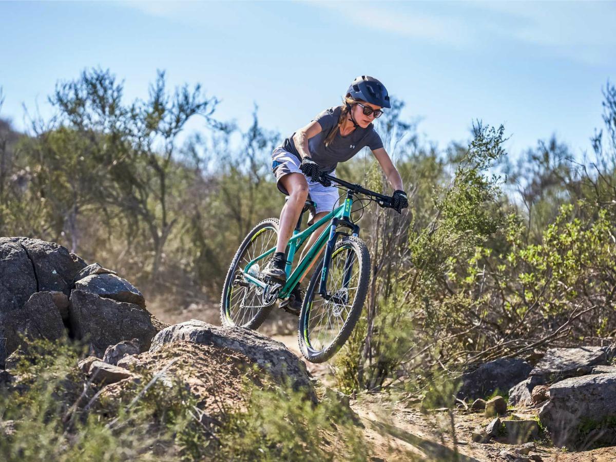 woman wearing helmet riding mountain bike down a rocky trail