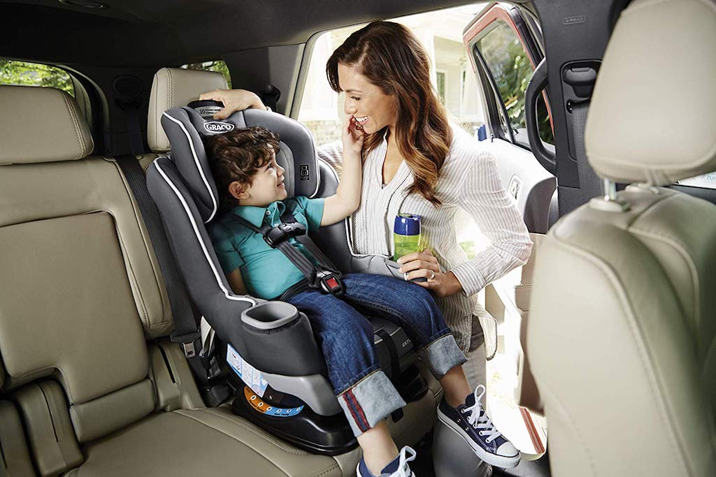 toddler sitting forward facing in a Graco car seat talking to a woman