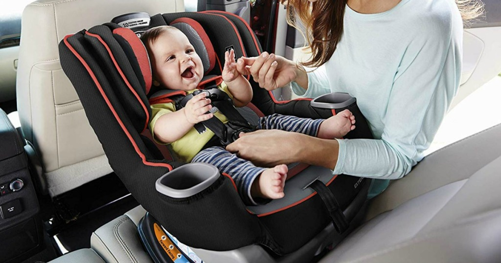 baby sitting rear facing in a Graco car seat holding a ladies hand