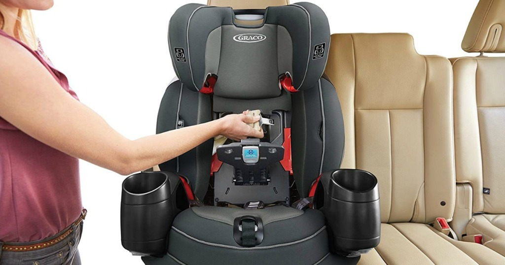 Graco car seat sitting on a tan leather car seat with a woman standing by it