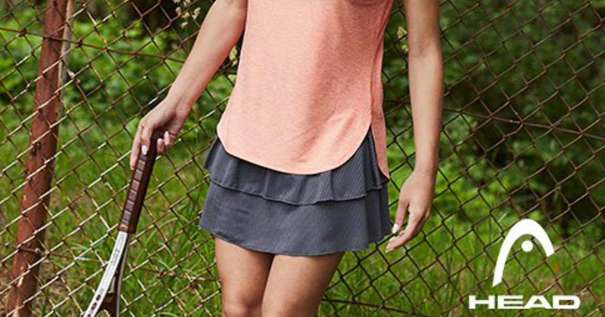 woman with tennis racket wearing grey tennis skirt and peach tank