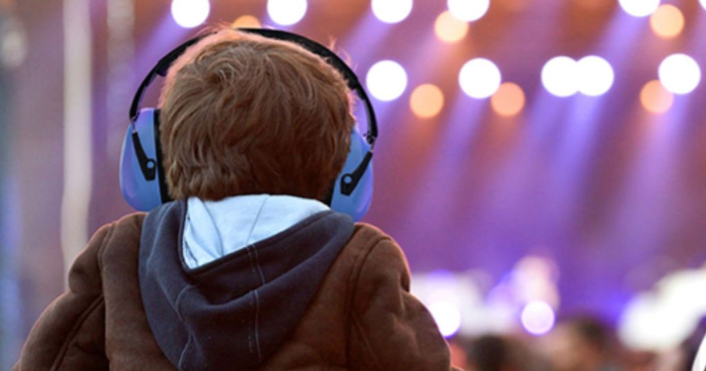 boy at concert wearing blue heartek earmuffs