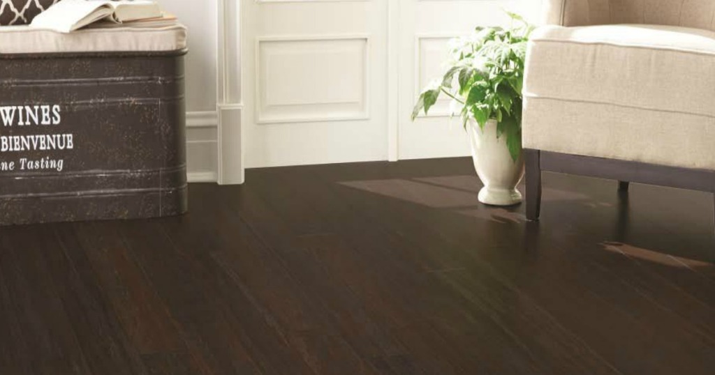 wood flooring in a room with a cream chair and a decorative trunk