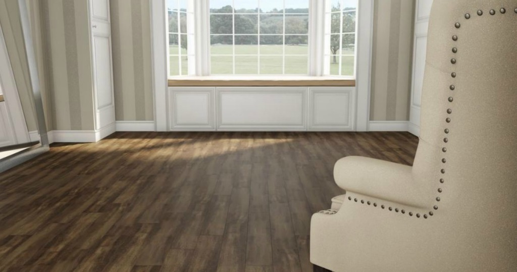 Hardwood Floors in a room with a cream chair and a big window