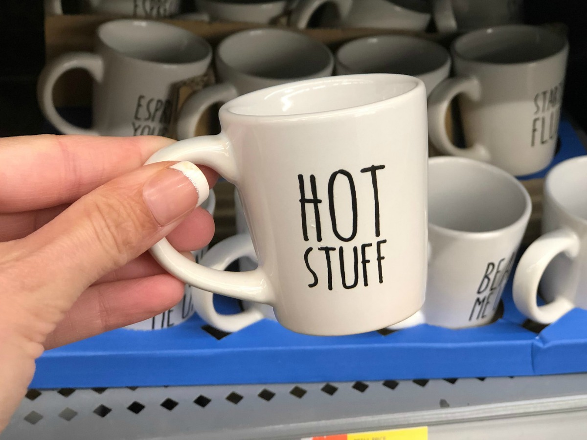 white espresso mugs with hot stuff written on it being held in a store