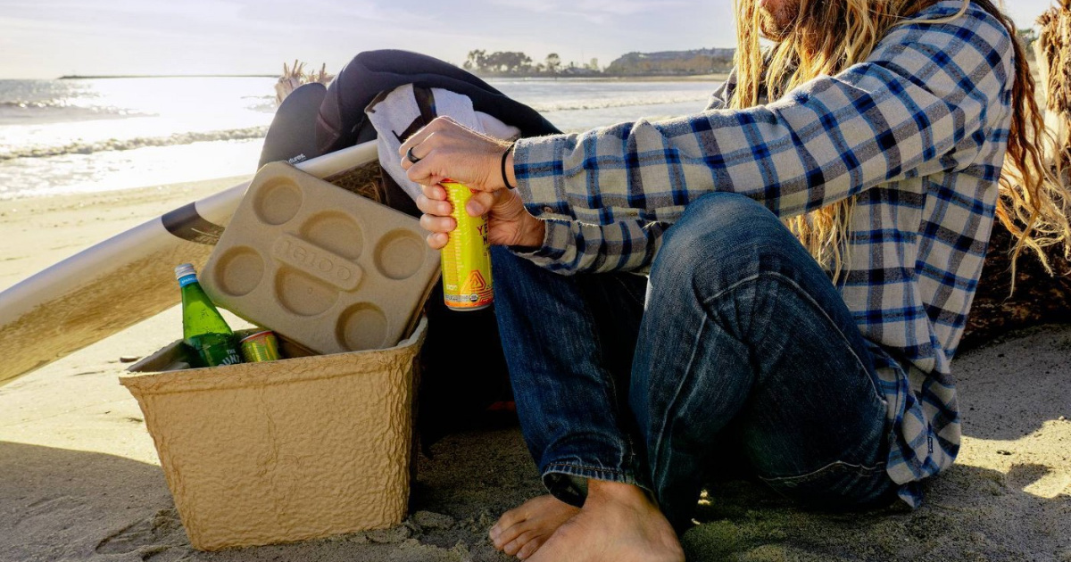 man sitting on beach with biodegradable cooler, surfboard and gear