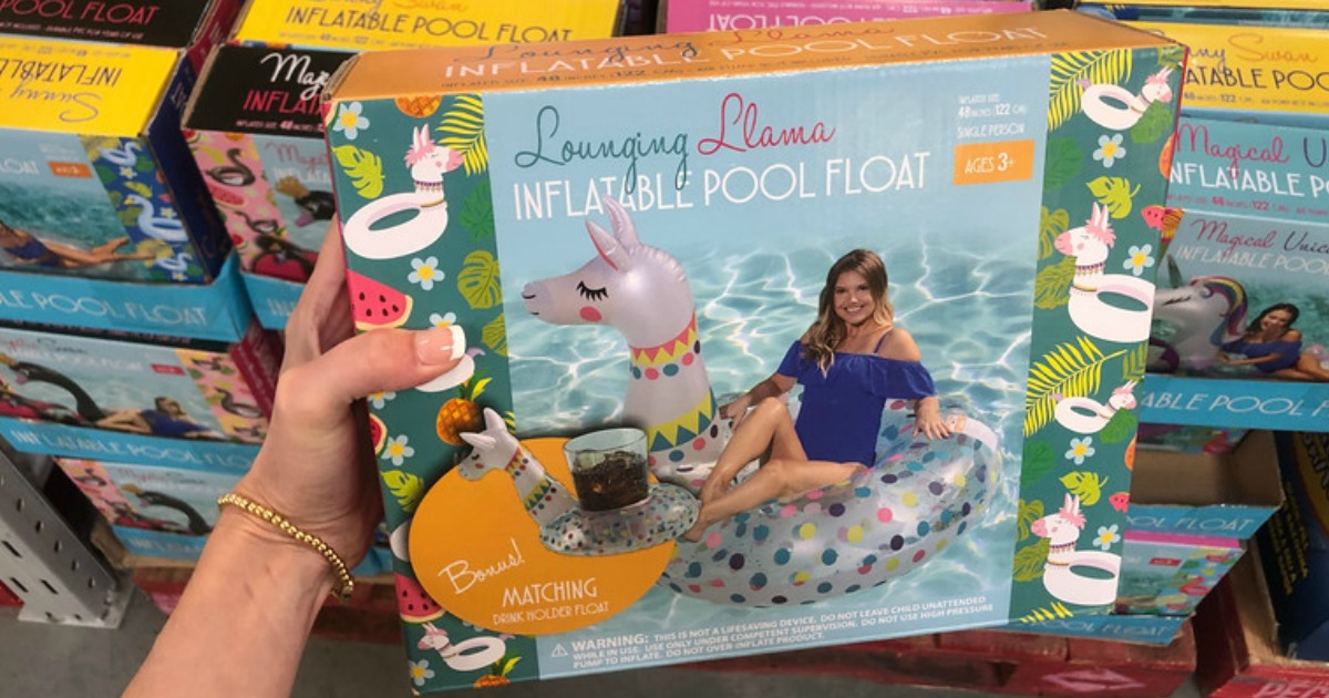 hand holding up lounging llama pool float with more floats behind it