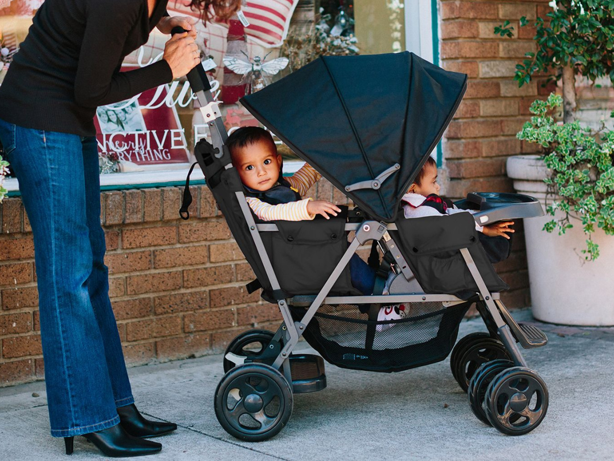 two babies in a double stroller, with a woman pushing