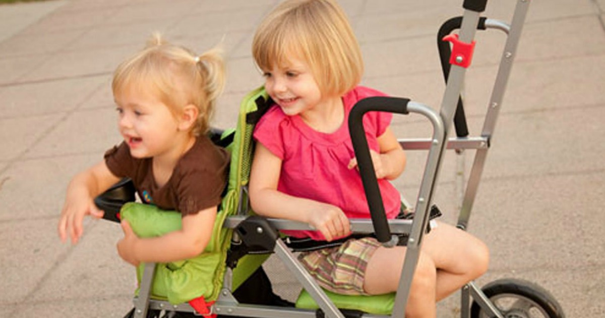 kids sitting in a green joovy tandem stroller