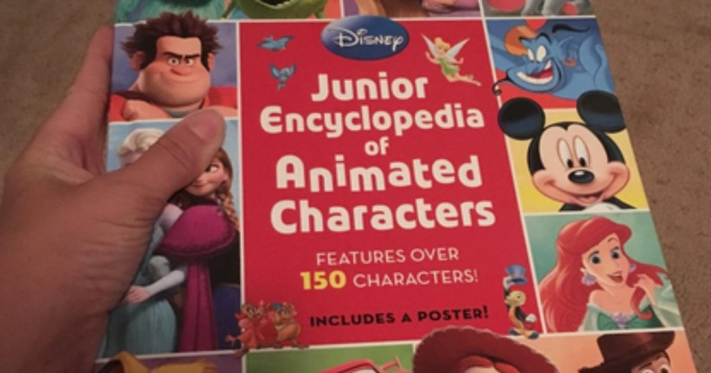 Person holding up cover of Disney Junior Encyclopedia of Animated Characters Hardcover Book