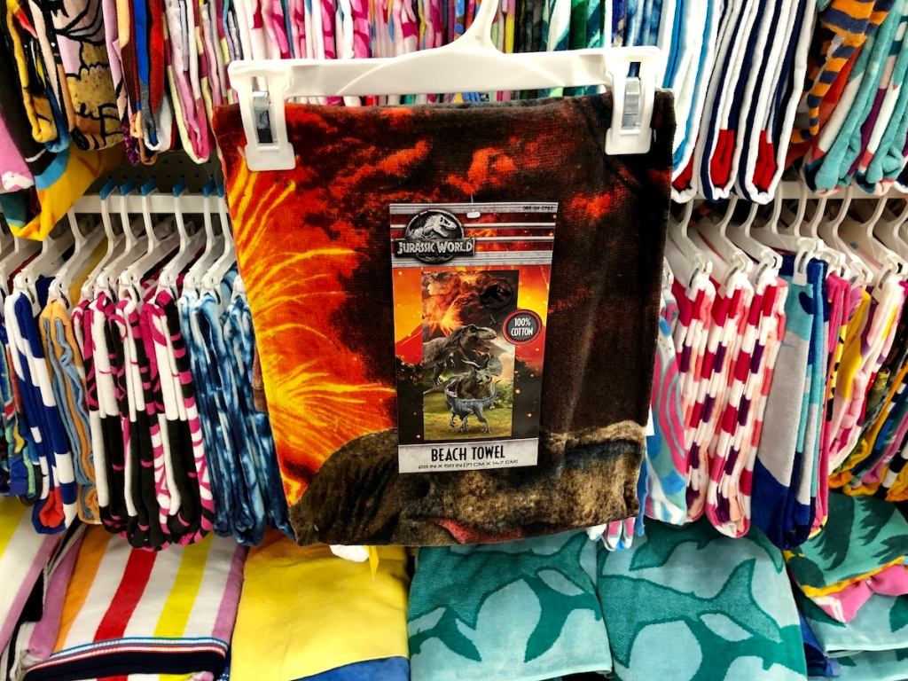 dinosaur beach towel in front of other towels