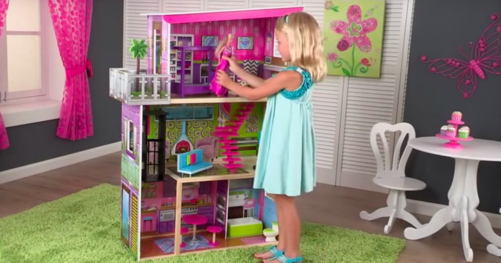 a girl playing with the KidKraft Super Model Dollhouse