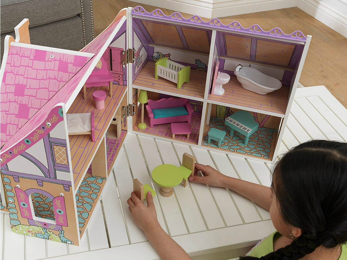 KidKraft Wooden Enchanted Forest Dollhouse opened with child playing with doll furniture