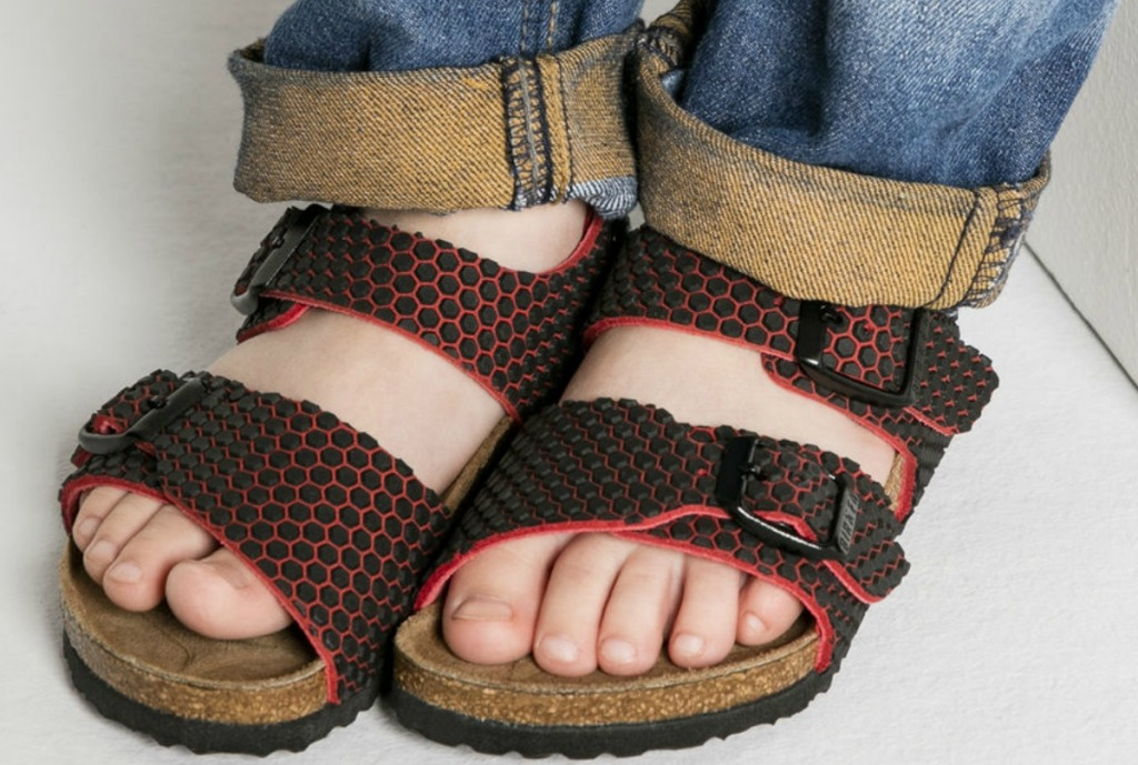 Kid wearing black and red Birkenstock sandals