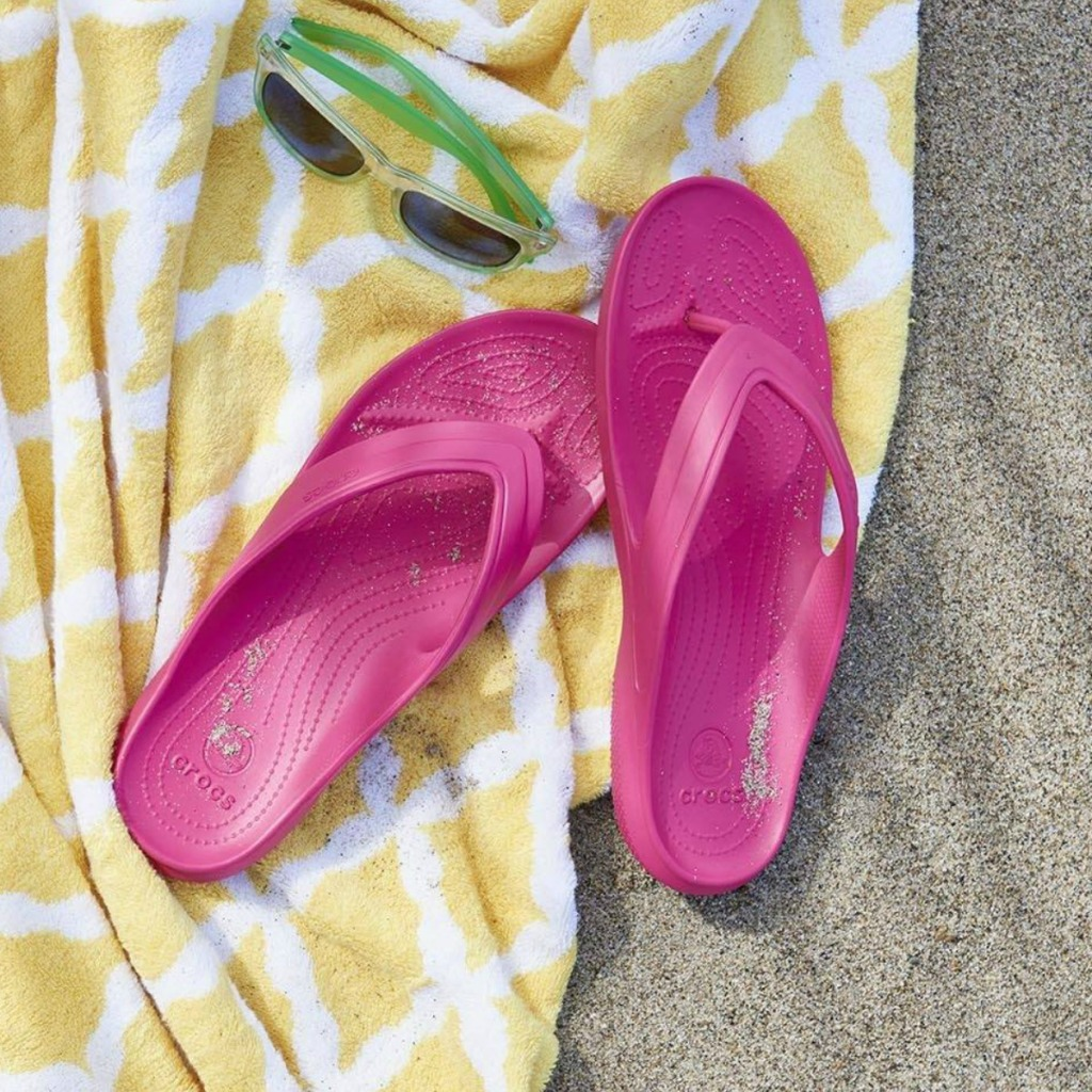 pink crocs sandals on yellow towel in the sand