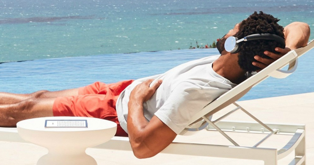 man listening to book on beach with Kindle Unlimited