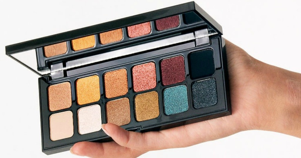 Woman's hand holding open eyeshadow palette