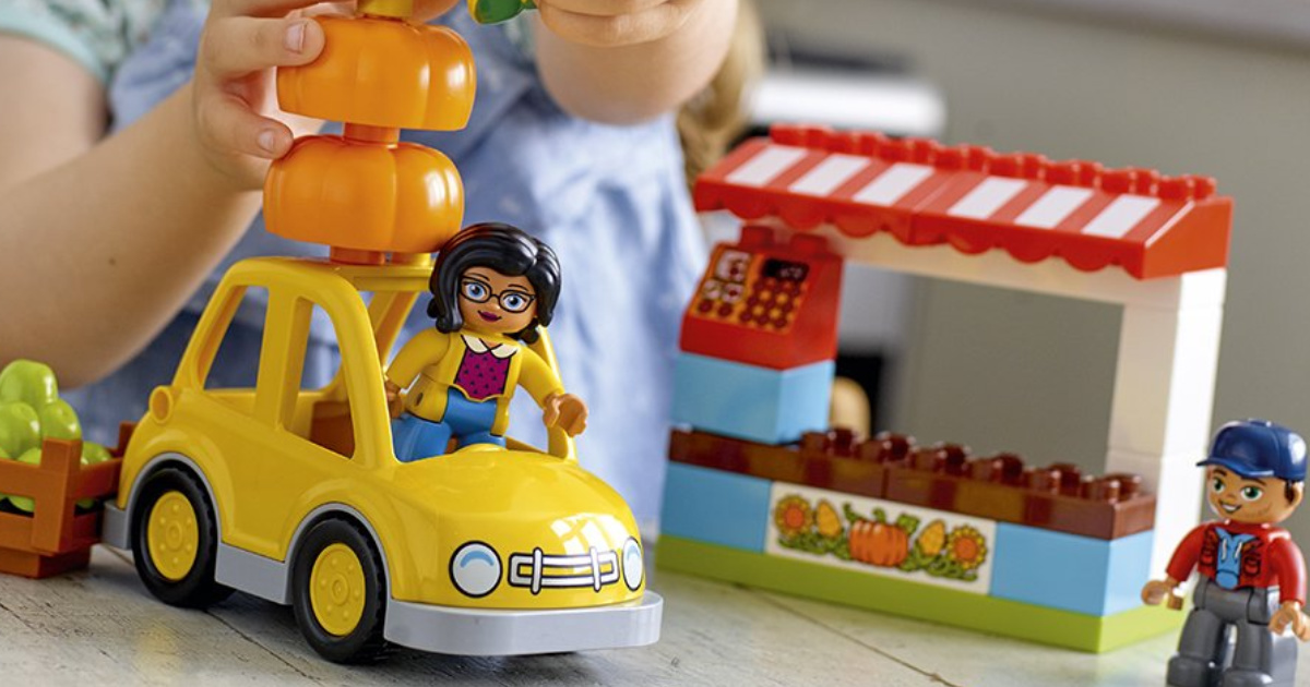 Little Girl Playing with a Yellow LEGO Car with a Fruit Stand