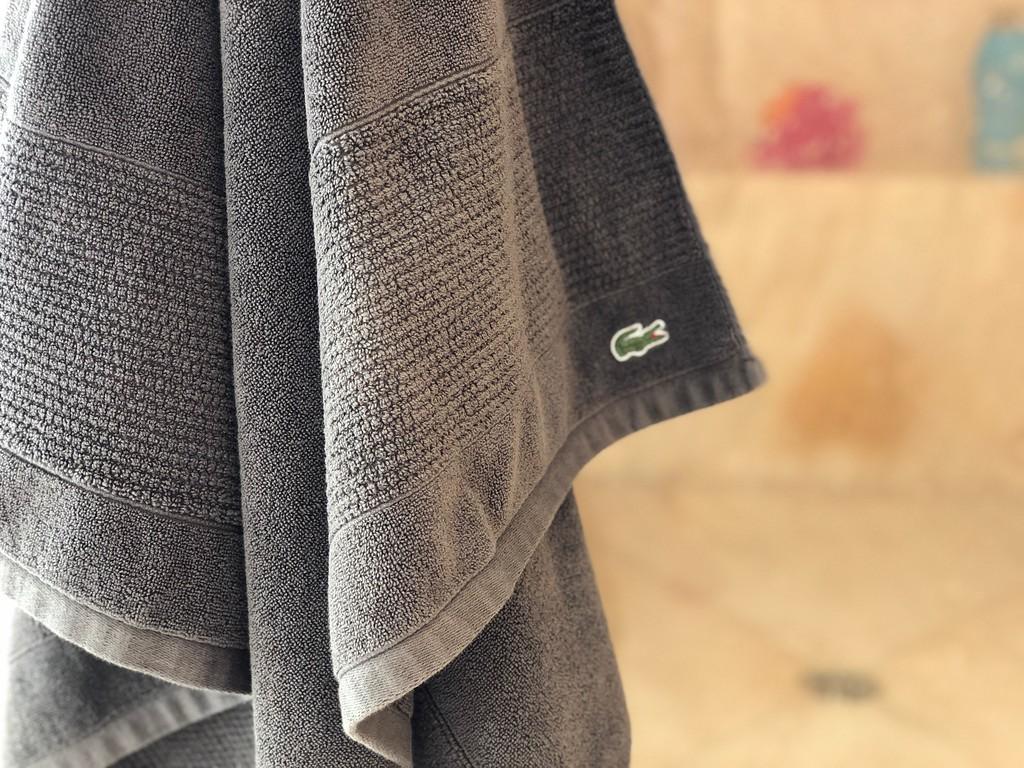 grey Lacoste bath towel hanging in a bathroom