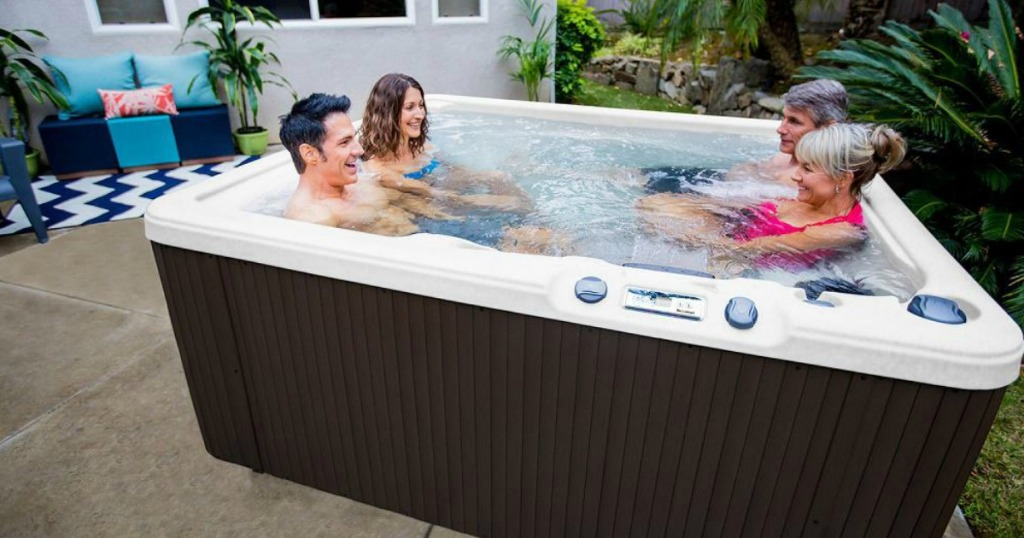 two couples sitting in Lifesmart Plus 5-Person Spa on a patio
