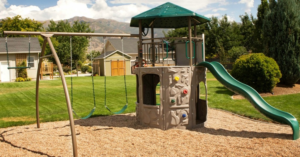 Large playset with a tower, swings, trapeze swing on a playground with bark