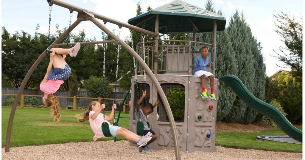 large playset with kids playing on the swings and clubhouse